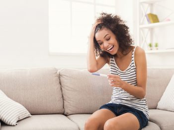 Excited young woman looking at a pregnancy test