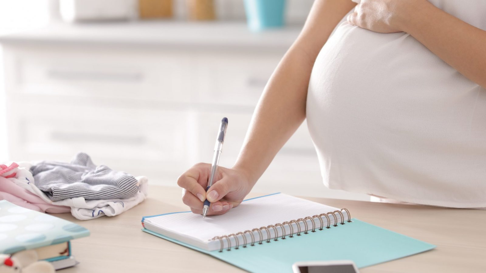 Pregnant woman writing in noteboook