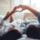 Couple-laying-on-bed-making-heart-shape-with-hands-trying-to-get-pregnant